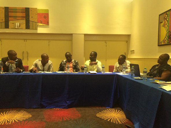Four men sit around a table at a conference in Accra