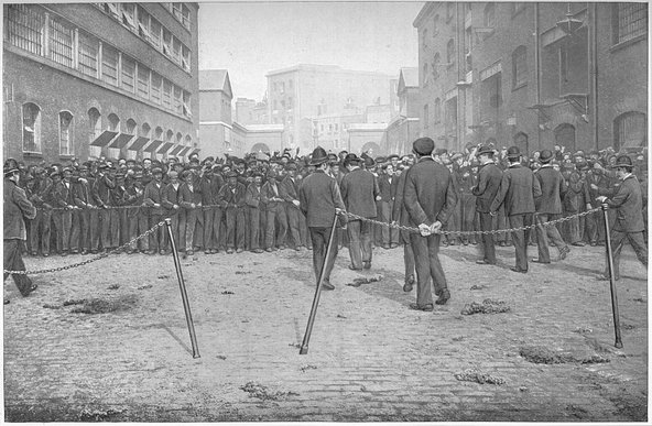 Eager for work, London, circa 1900 (1901). Men lining a fence looking to work at the London Docks. Image credit: The Print Collector/Getty Images.
