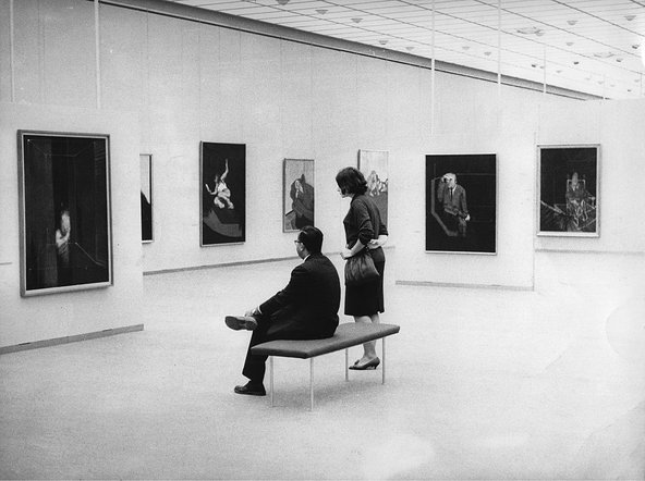 Black-and white-photograph of two people with their backs to the camera, looking at the Francis Bacon paintings hung before them in the gallery space.