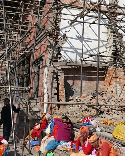 People sit outside scaffolding and a collapsed building in Kathmandu