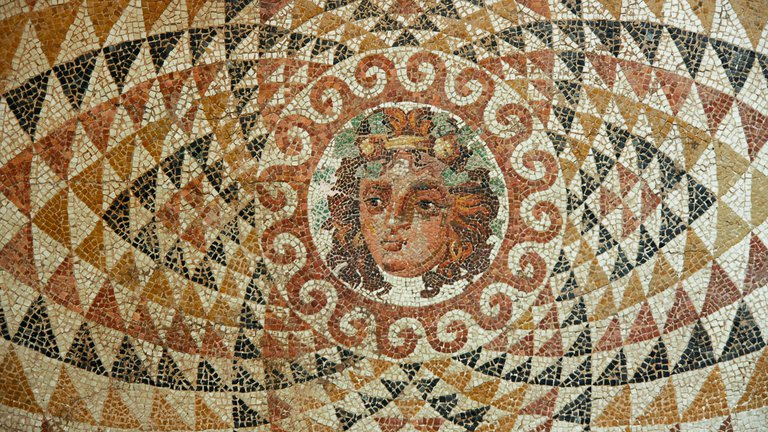 A colourful mosaic with the face of the Roman god Dionysus depicted in the centre, wearing a vine wreath and surrounded by a geometric pattern.
