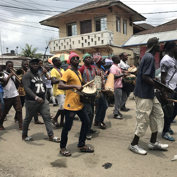 Young men in the Niger Delta in procession with musical instruments