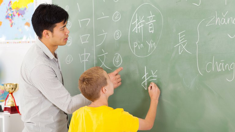 School teacher helping young boy writing chinese