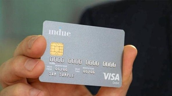 A hand holds up a sample of the cashless debit card