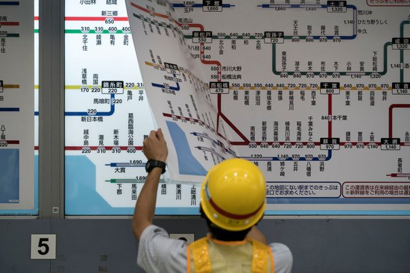 An employee replaces a map with train fares at an East Japan Railway Co. train station on October 1, 2019 in Tokyo, Japan. Japan