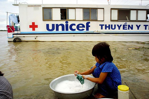 A young girl washes clothes near a UNICEF-funded medical boat anchored at the flooded district of Tam Nong in Southern Mekong delta province of Dong Thap. Image credit: HOANG DINH NAM/AFP/Getty Images.