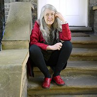 Professor Dame Mary Beard FBA shown sitting on some steps and smiling to the camera, wearing a red coat and red shoes.